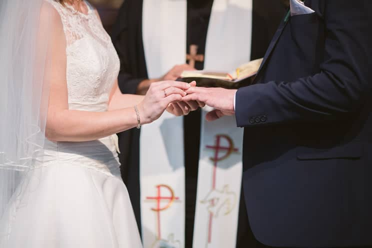 Bride putting wedding ring on grooms finger at the altar