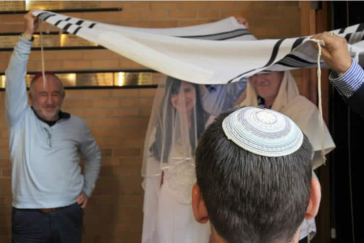 Jewish wedding ceremony holding the cloth above the bride and groom