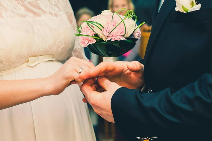Bride putting ring on grooms ring finger.