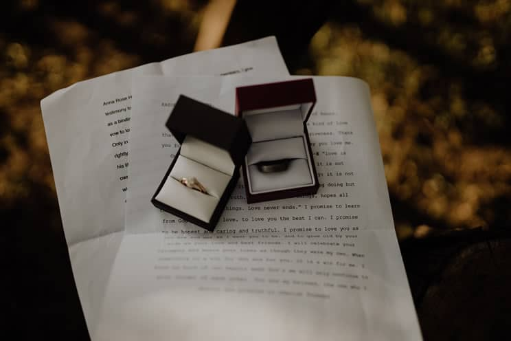 Wedding vows on paper with two ring boxes and rings on top