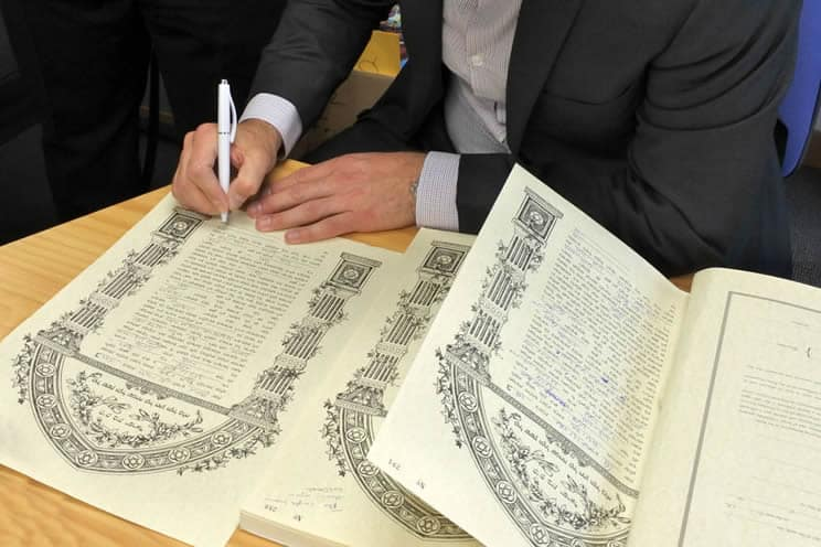 Jewish groom signing legal document at the wedding