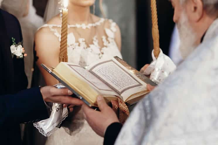 Catholic priest reading from the bible during wedding ceremony