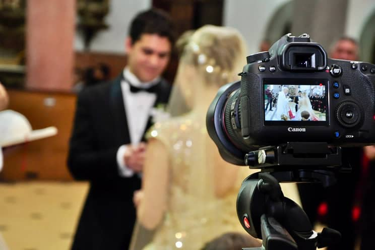 Wedding couple out of focus with camera on tripod in front
