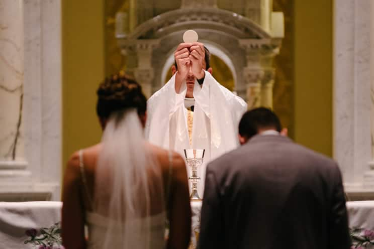 Catholic bride and groom in front of priest at wedding