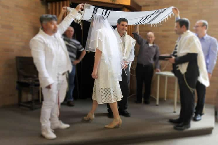 Jewish couple walking under the chuppah during their wedding ceremony