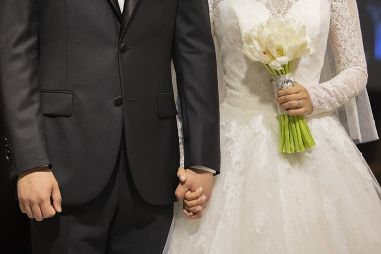 Wedding couple with bride holding flowers