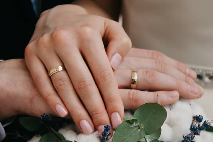 Jewish couple with hands on each other hands wearing gold rings