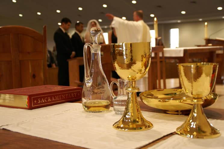 Catholic couple and priest in background to holy cup