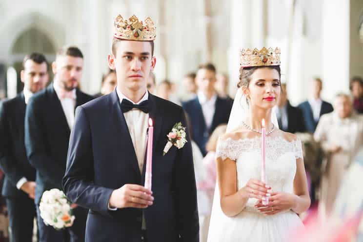 Orthodox wedding couple wearing Stefana crowns and holding candles