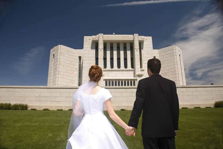 Mormom groom and bride holding hands outside a Mormon temple