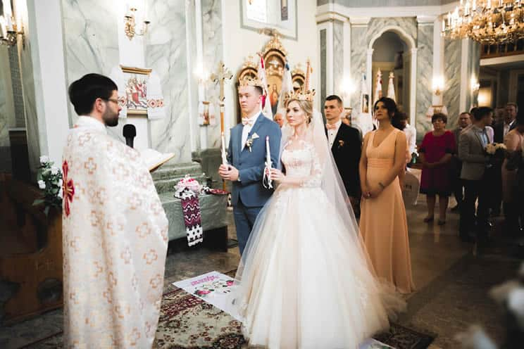 Orthodox wedding couple wearing Stefana crowns and carrying candles