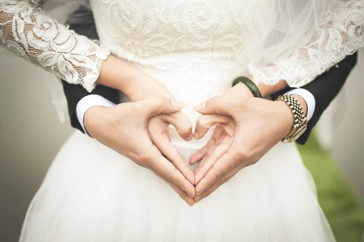 Couple using their hands to make heart symbol